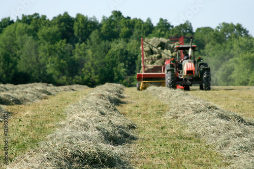 Freshly Baled Hay – A tractor pulls a hay baler and wagon