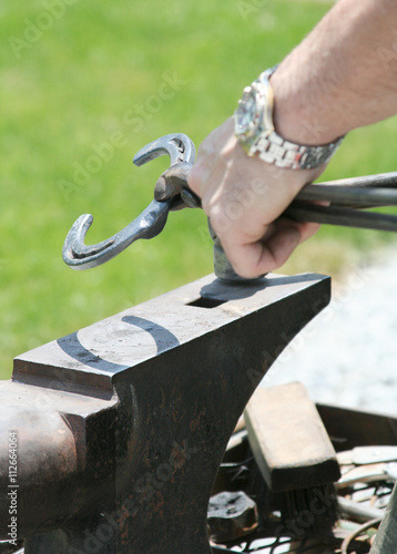 Shaping a Horsehoe – A blacksmith farrier prepares to shape a