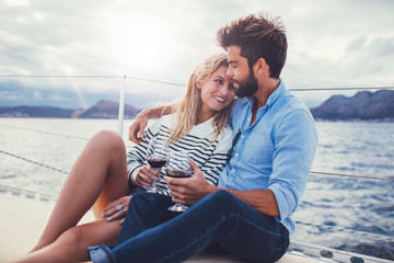 Romantic couple holding wine glasses on yacht