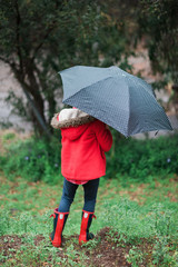 Child in red coat and boots under umbrella