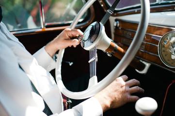 Man sitting in driving seat of vintage car