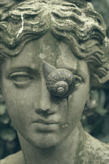Statue with snail crawling across face