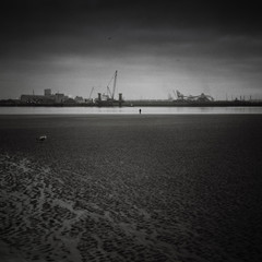 B&W Photo of a man on a beach, staring at an industrial scene