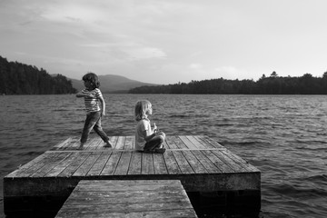 Two young brothers on jetty, one sitting meditating, the other skimming pebbles, black and white