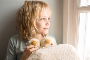 Young boy holding soft toys, sitting beside window, looking at view