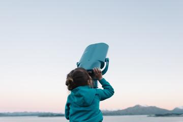 Young girl looking through binoculars, outdoors