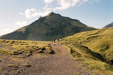 Hikers on a trail on a green mountain top in Iceland