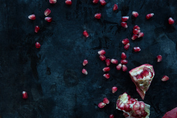 Scattered pomegranate seeds on a dark surface