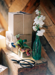 Gift boxes and glass bottle with flowers, still life