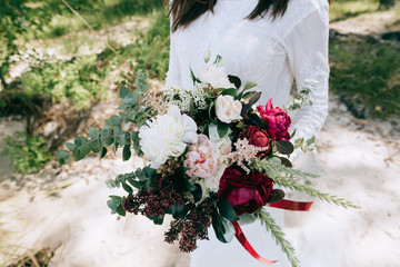 Bride in a white dress holding a beautiful Eucalyptus white pink and red peonies wedding bouquet in her hands