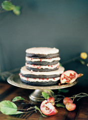 Layered chocolate cake with cream and pomegranate seeds