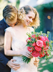 Bride with bouquet and groom kissing her neck