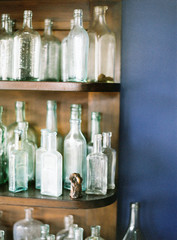 Vintage glass bottles on wooden shelf