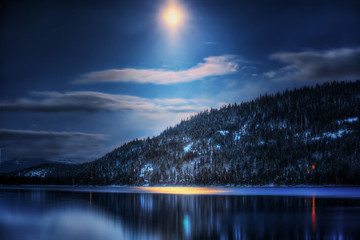 Tree covered mountain by lake in moonlight