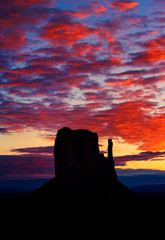 Silhouette of rock formation against dramatic orange sky