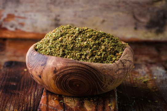 Mixed east spice - zaatar or zatar in vintage bowl on wooden background. Selective focus