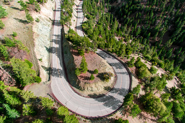 Aerial drone view of hairpin bend in road through mountains