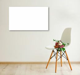 Bouquet of roses on a white chair and picture frame in room