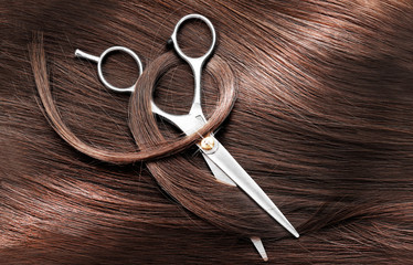 Hairdresser's scissors with dark brown hair, close up