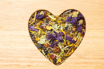 Dried herb leaves heart shaped on wooden surface