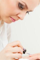 Female beautician making nails.