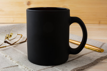 Black coffee mug mockup with glasses and pen