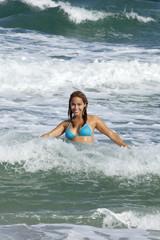 Pretty woman in sexy light blue bikini playing in the ocean
