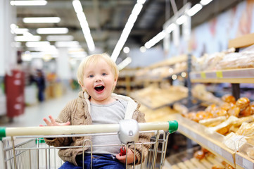 Tddler boy sitting in the shopping cart in a supermarket
