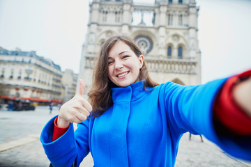 Beautiful young tourist in Paris, making funny selfie
