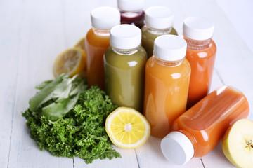 Diet concept: vegetable juices in bottles on wooden background