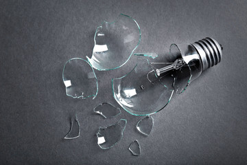 Broken light bulb on grey background