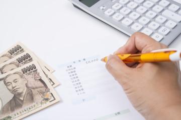 家計簿で生活費の予算を立てる主婦の手元