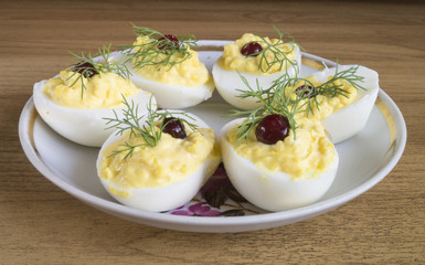 Stuffed egg with cranberry and green dill