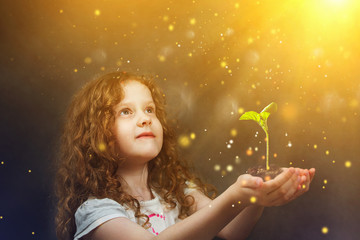 Little girl holding young green plant in sunlight. Ecology conce