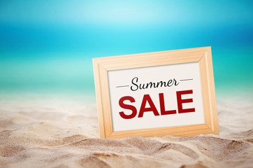 Summer sale Concept. Close up wooden picture frame and summer sale text on the beach