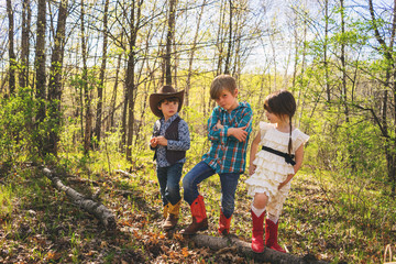 Three children dressed up as cowboys