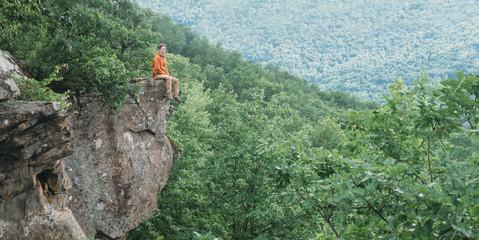 Traveler sitting on cliff