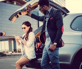 International couple with smartphone near car.