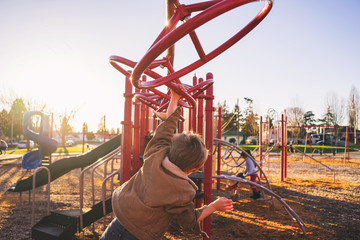 Rear view of boy swinging on monkey bars in playground