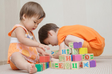 Brother and sister playing with toy cubes
