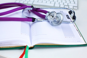 Stethoscope lying on a notebook computer in the background and books