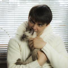 boy hugging a beautiful gray cat