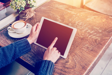 Close up hand woman using tablet in coffee shop with vintage ton
