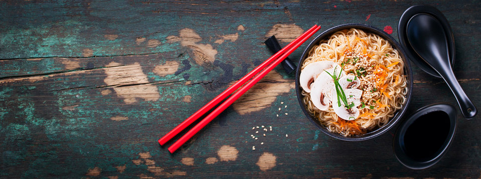 Asian noodles with vegetables and mushrooms, soy sauce, sticks on a dark background, top view with copy space