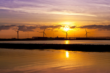 Wind turbines near seashore at sunset