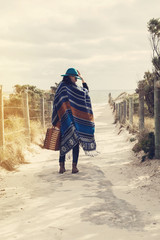 Young hipster girl in poncho with vintage suitcase