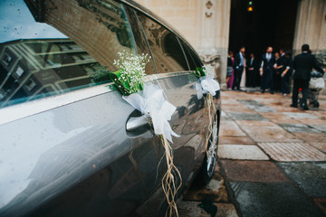 Grey wedding car decoration with people waiting in a church in the background.
