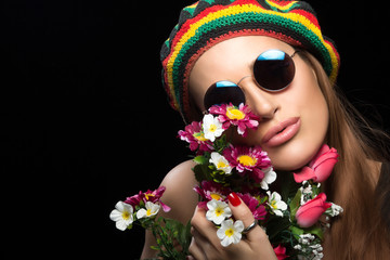 Young woman in sunglasses and rasta hat holding flowers