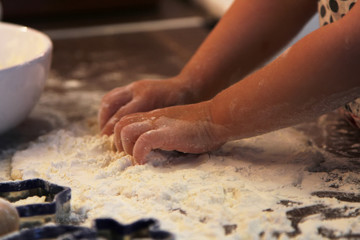 Closeup photo of child hands making  dough for cookies