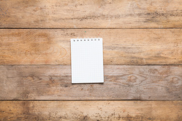 Blank notebook on wooden background.